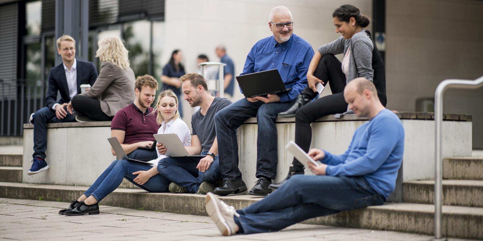 Mehrere Personen sitzen auf dem Campus der FernUniveristät mit Laptops