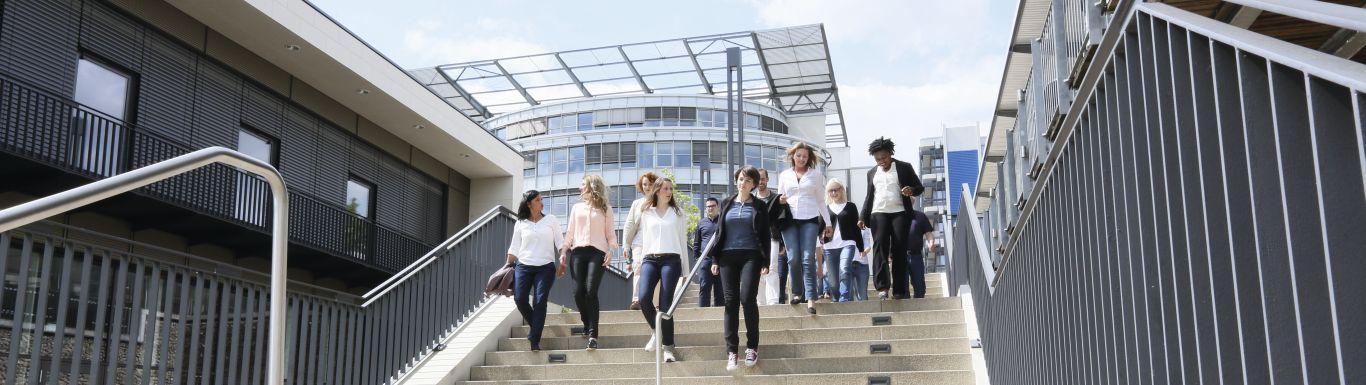 Mehrere Personen gehen auf dem Campus der FernUniversität eine Treppe runter